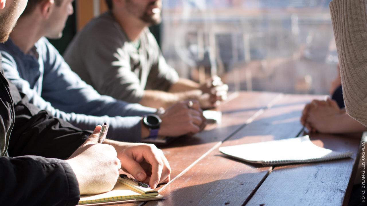 Selbsthilfegruppe sitzt am Tisch. ffs Café Okay.