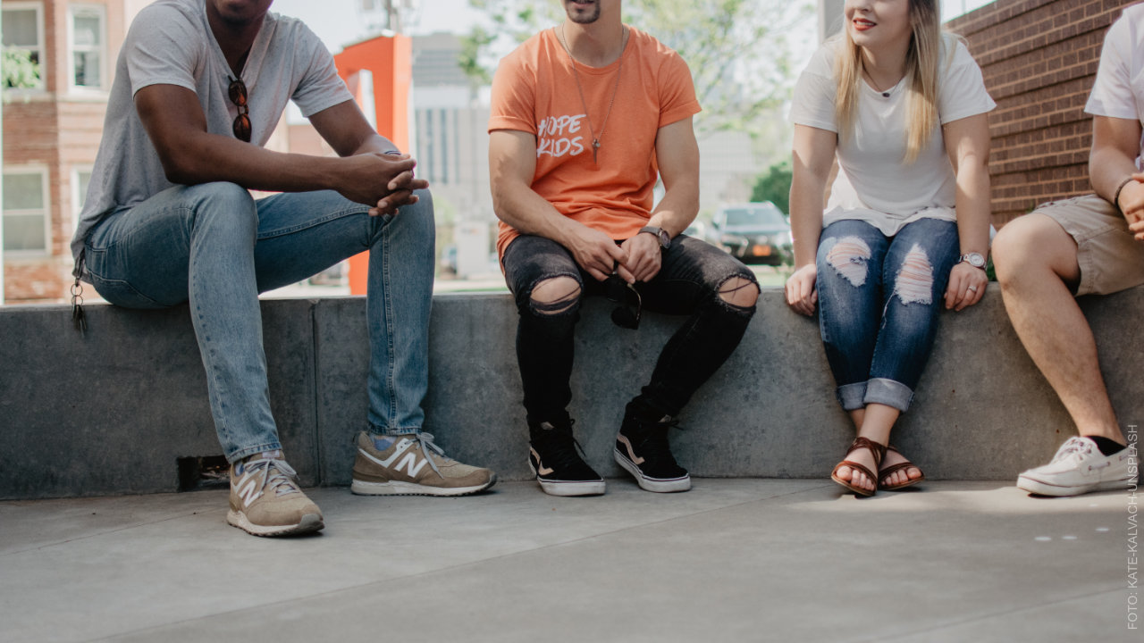 Personen sitzen vor dem Gebäude. ffs Gleis1